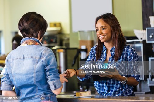 Shop employee accepting payment on digital tablet credit card reader