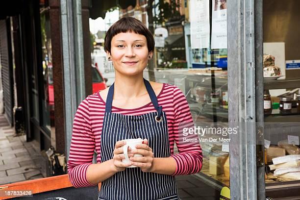 Shop employee has a coffee break in front of shop.