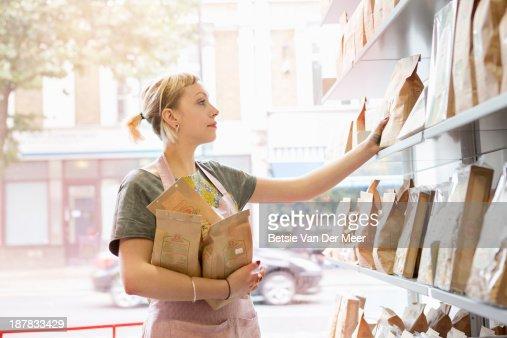 Shop employee stacking shelves in delicatesse shop