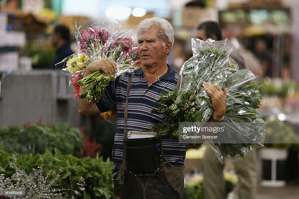 A shop keeper carries flowers to his stall during Valentines Day at Sydney Flower Market on February 14, 2013 in Sydney, Australia. Due to an unusually hot January in Australia an increasing number of roses have been sourced from South America and Africa to ensure Valentines supplies don't run out.