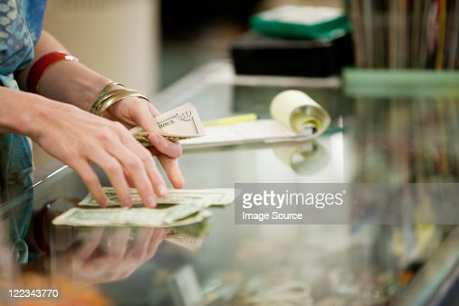 Shop keeper counting money in shop