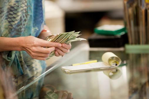 Shop keeper counting money in shop : Stock Photo