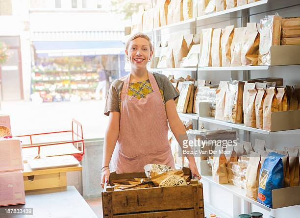 Shop keeper holding crate with food bags..