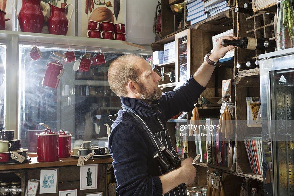 Shop keeper placing bottles in rack. : Stock Photo