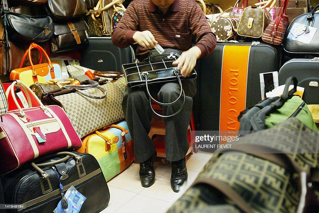 counterfeit prada - A shop keeper polishes a fake Prada bag while seating among other ...