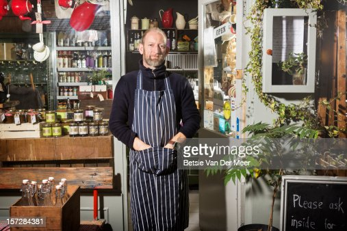 Shop keeper standing in front of shop. : Stock Photo