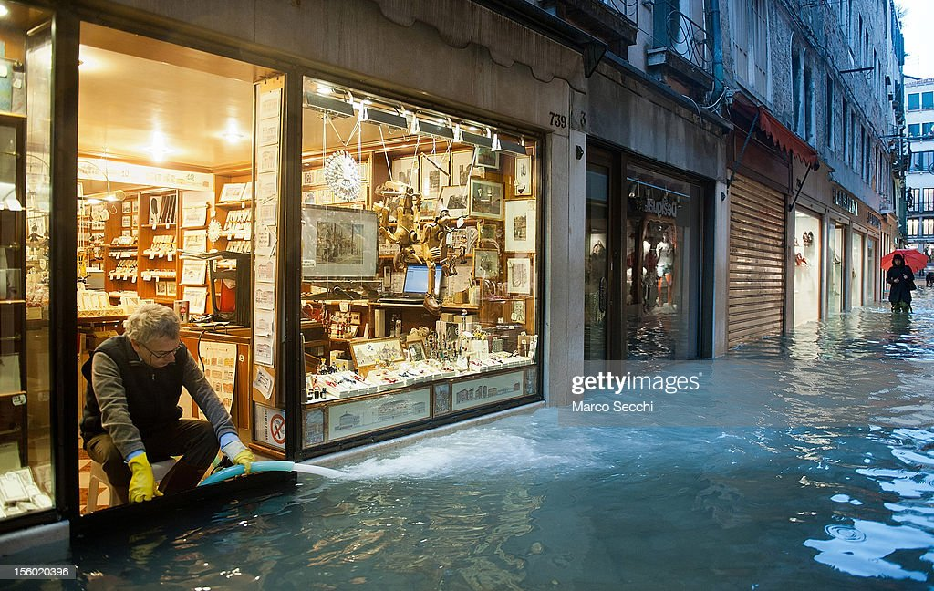 A shop keeper tries to maintain the water level inside his shop at a minimum during the exceptional High Water on November 11, 2012 in Venice, Italy. More than 70% of Venice has been been left flooded, after the historic town was hit by exceptionally and unexpected high tide. The sea level rose very quickly to 150 due as well to strong southerly wind and heavy rain.