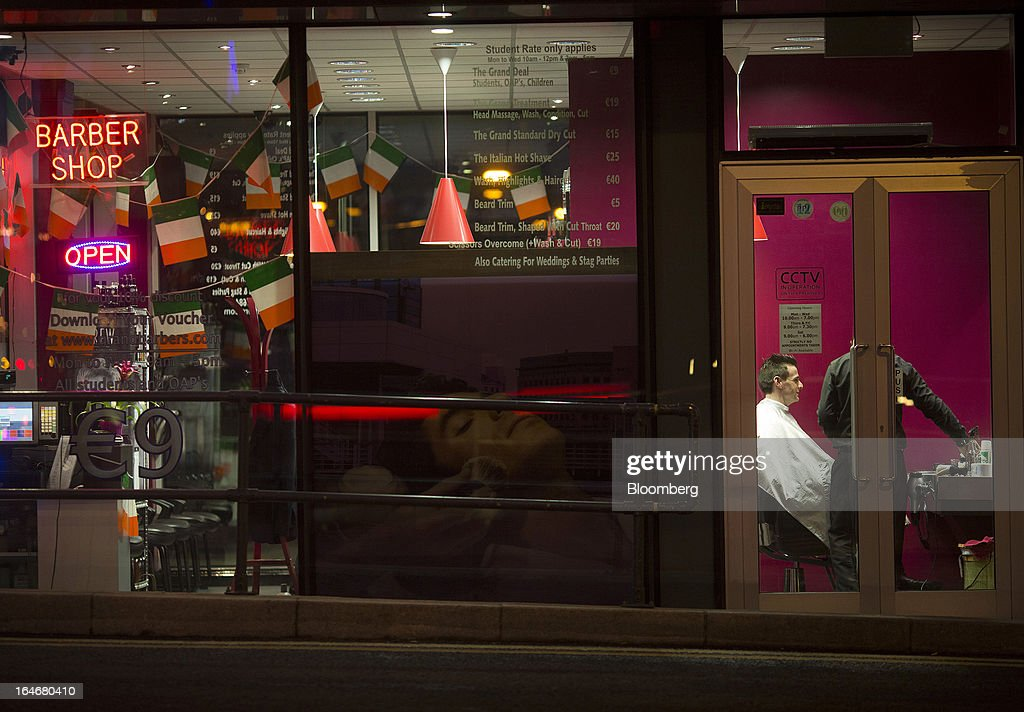 Shop lighting illuminates a man siting for a haircut inside a barber shop in Dublin, Ireland, on Friday, March 15, 2013. Ireland's renewed competiveness makes it a beacon for the U.S. companies such as EBay, Google Inc. and Facebook Inc., which have expanded their operations in the country over the past two years. Photographer: Simon Dawson/Bloomberg via Getty Images