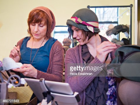 Shop owner checks the cash receipts with assistant : Stock Photo