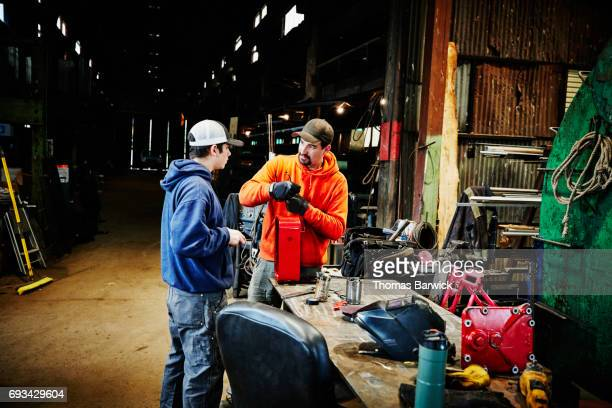 Shop owner discussing project with employee in metal workshop