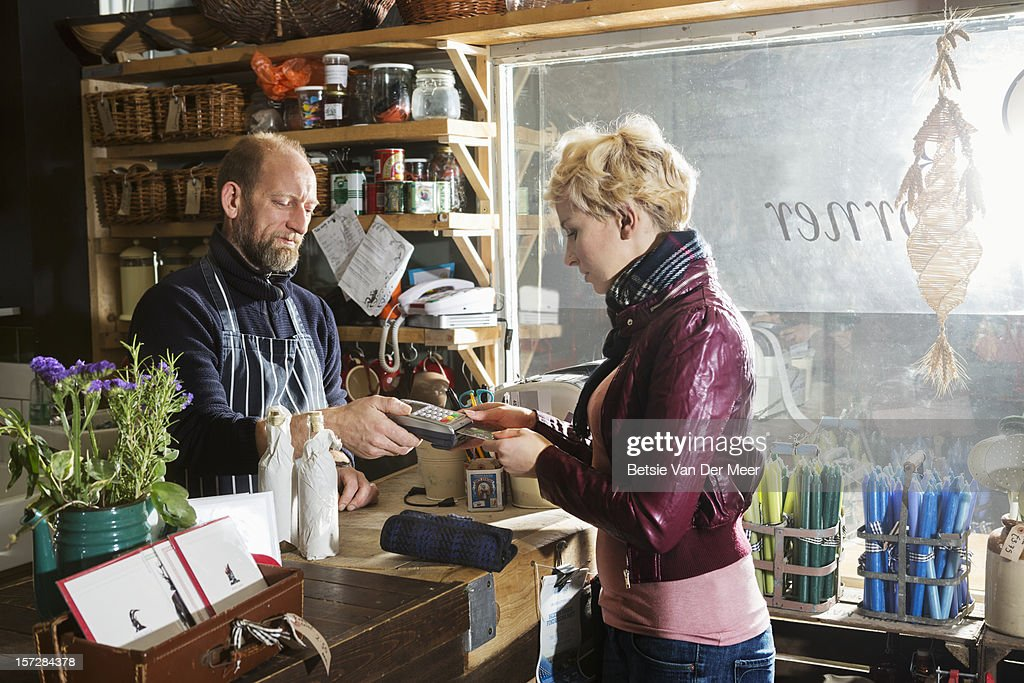 Shop owner hands pin acceptance device to customer : Stock Photo