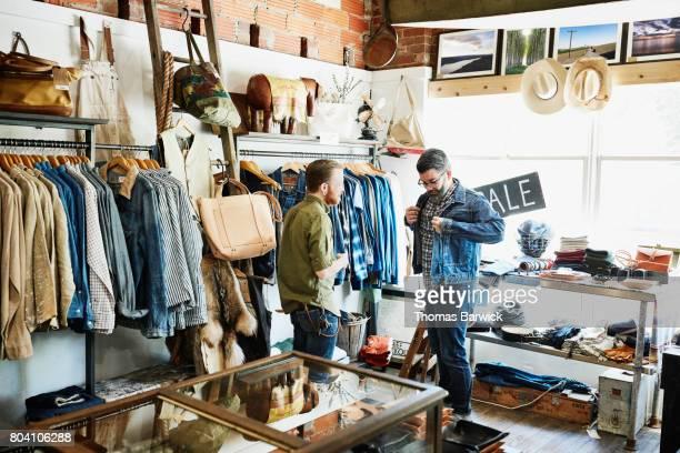 Shop owner helping customer try on denim jacket in mens boutique