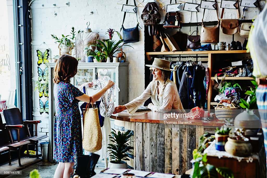 Shop owner in discussion with customer at counter