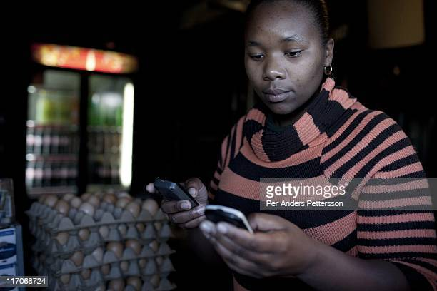 A shop owner makes a banking transaction on her mobile phone on May 5 2011 in Khayelitsha the poorest and largest township outside Cape Town South...