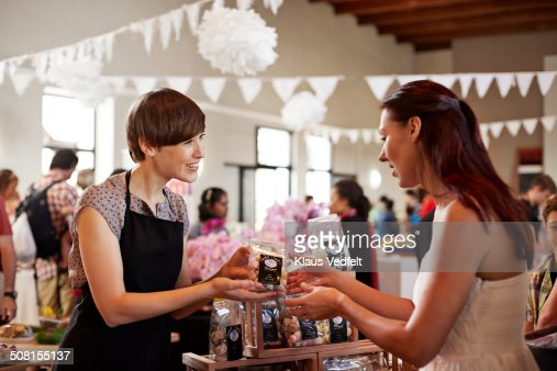 Shop owner passing bag of meringues