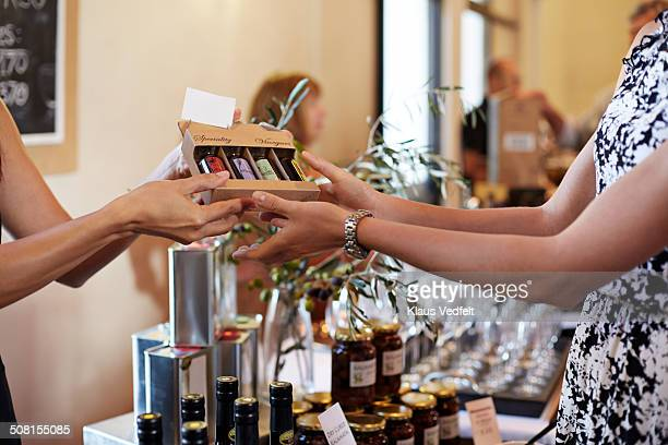 Shop owner passing box of small vinegars
