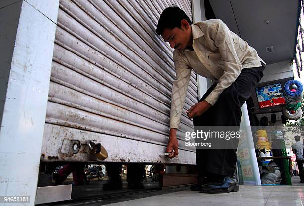 A shop owner pulls up the shutter of his shop situated outside Mumbai India on Thursday Nov 29 2007 India's economy grew last quarter at the slowest...