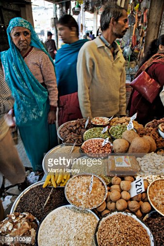 Shop owner selling a variety of spices in his small shop, Delhi, India.