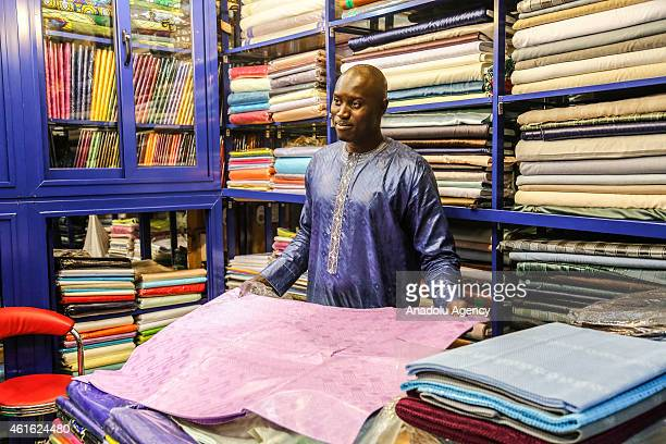 A shop owner sells Boubou fabrics a traditional clothing of Senegal in Dakar on January 9 2015 In the outskirts of Dakar in Castor Bourguiba's street...