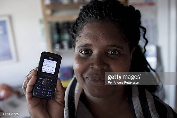 A shop owner shows her mobile phone with the confirmation of a two Rand transaction on May 5 2011 in Khayelitsha the poorest and largest township...