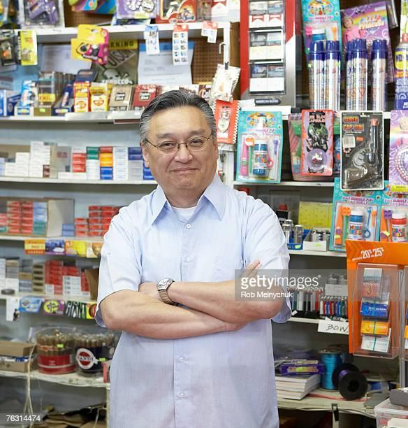 Shop owner smiling, behind shop counter, portrait