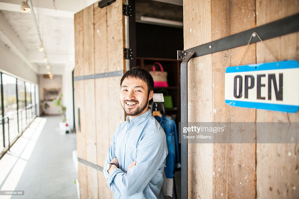 A shop owner standing in front of his shop : Stock Photo