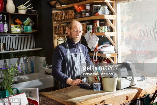Shop owner standing in shop behind counter : Stock Photo