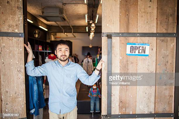 A shop owner standing in the door of his shop