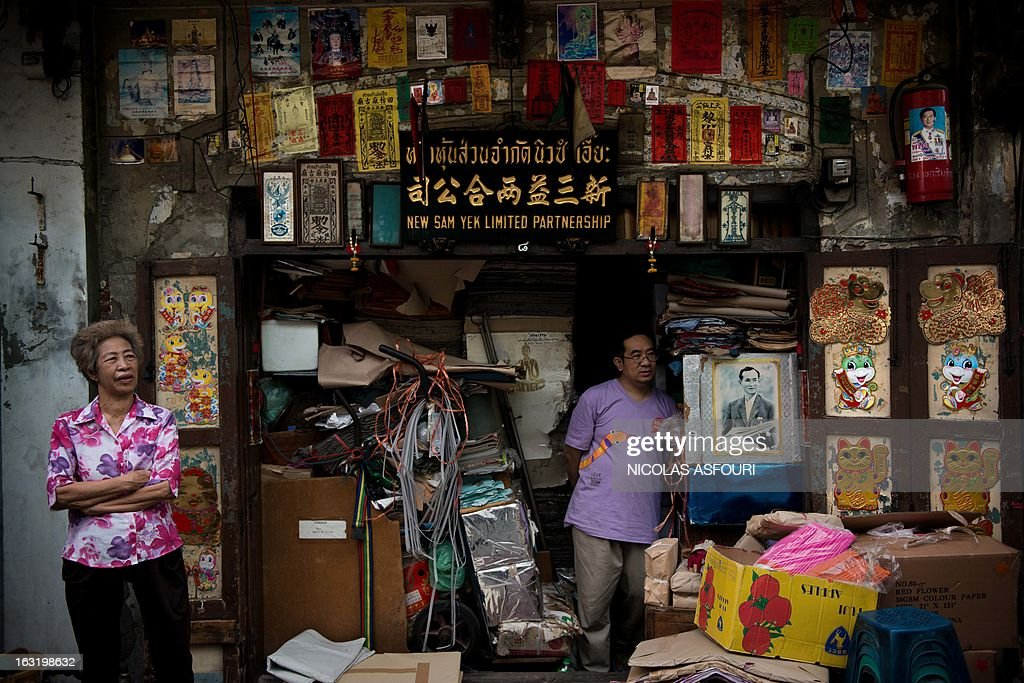 A shop owner (L) stands outside her shop in the Chinatown area of Bangkok on March 6, 2013. Packed with market stalls, street restaurants and a dense concentration of gold shops the area is a popular tourist destination in Thailand's capital. AFP PHOTO / Nicolas ASFOURI
