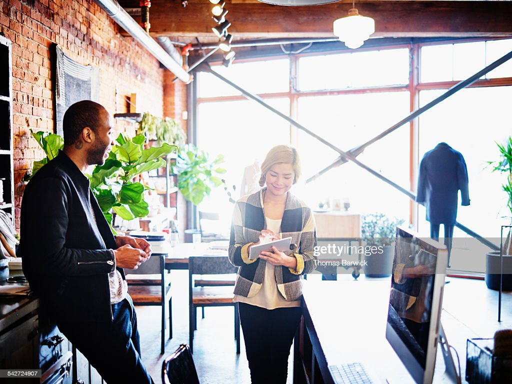 Shop owners checking inventory on digital tablet : Stock Photo