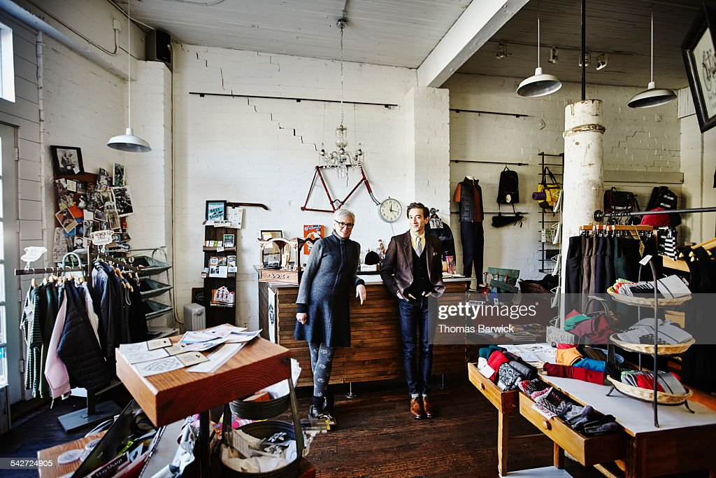 Shop owners standing together in clothing boutique