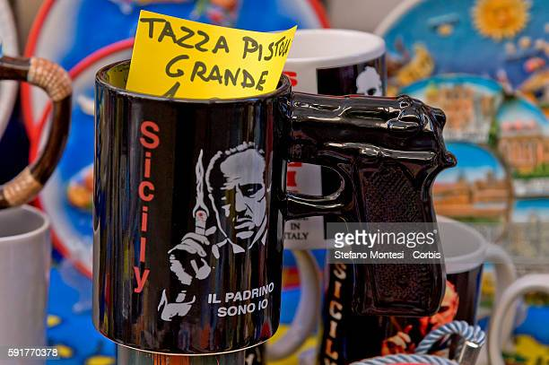 A shop sells souvenirs cup with with the printed posters of the movie 'The Godfather' and how to handle the butt of a gun on August 13 2016 in...