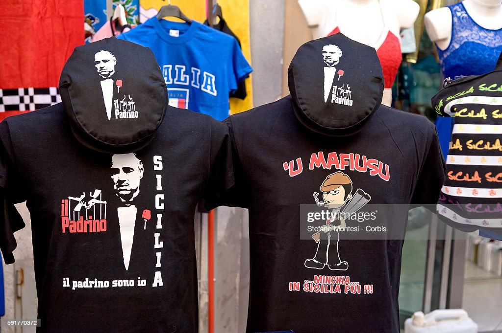 A shop sells tshirt with printed of the movie poster 'Il Padrino' and tshirt with printed 'U mafiusu Sicily' with the traditional Sicilian headgear...