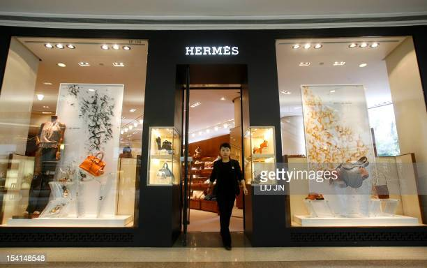 A shop staff walks out of an outlet of the French fashion brand Hermes in Shanghai 19 June 2007 The luxury icon opened a new store to mark its 10th...