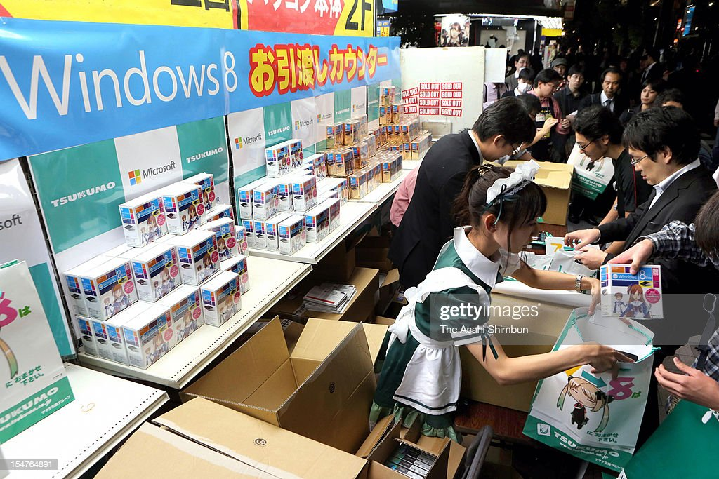 A shop staff wearing maid costume hands Microsoft new operating system Windows 8 at a shop in Akihabara on October 26, 2012 in Tokyo, Japan.