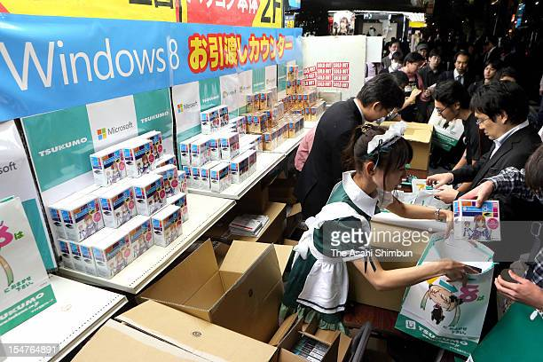 A shop staff wearing maid costume hands Microsoft new operating system Windows 8 at a shop in Akihabara on October 26 2012 in Tokyo Japan