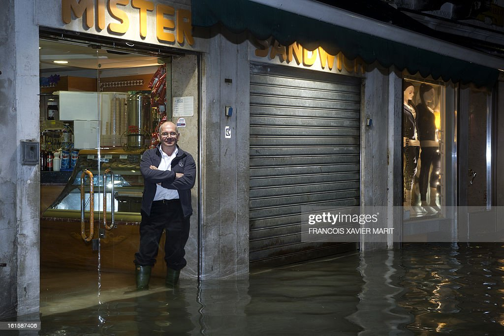 A shop tender stands as the water rises in a street during an acqua-alta (high-water) late on February 11, 2013 in Venice. The 'acqua alta', a convergence of high tides and a strong sirocco, reached 143 centimetres around midnight.