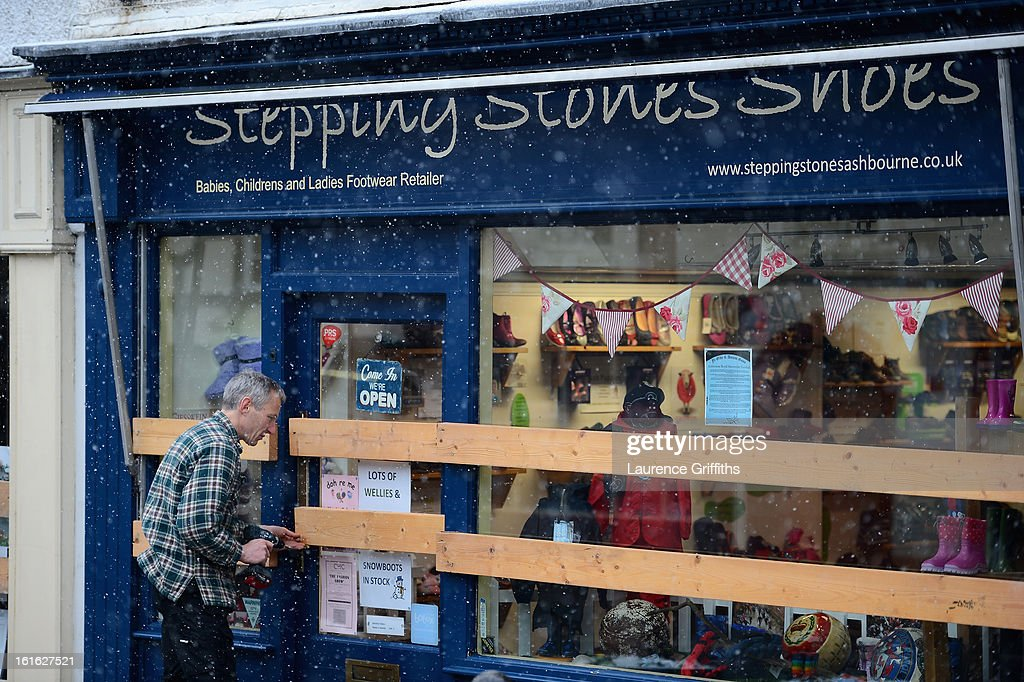 A shop window is protected during the annual Ash Wednesday 'no rules' football match on February 13, 2013, in Ashbourne, England. First played in the 17th Century between teams from opposite ends of the Derbyshire town, hundreds of participants aim to get a ball into one of two goals that are positioned three miles apart at either end of Ashboune. The match starts on Shrove Tuesday and can last until 10 PM. If a goal is scored before 6 PM, then a new ball is 'turned up' again and a new game started. If the goal is after 6 PM then the game ends for that day and continues into the next day - known as Ash Wednesday.