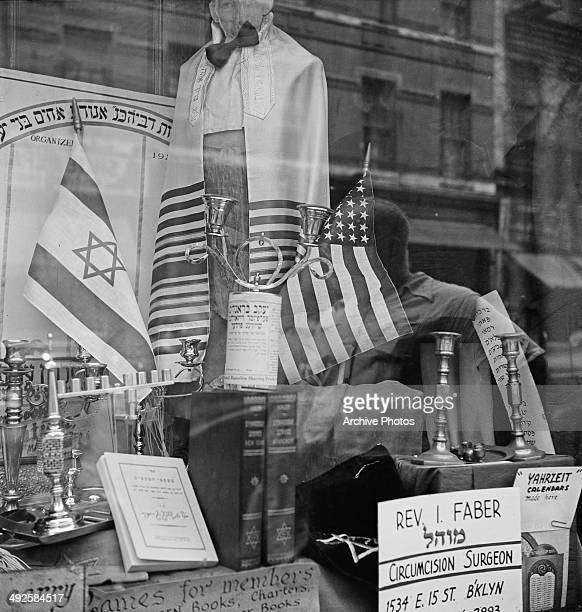A shop window selling Jewish items on the Lower East Side of Manhattan New York City USA circa 1955 A US flag is positioned opposite the flag of...
