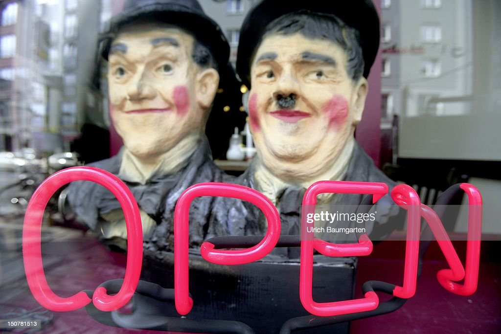 GERMANY, BERLIN, Shop window with neon sign writing OPEN and the heads of the two comedians Laurel and Hardy in a pub at the Rosenthaler street in Berlin.