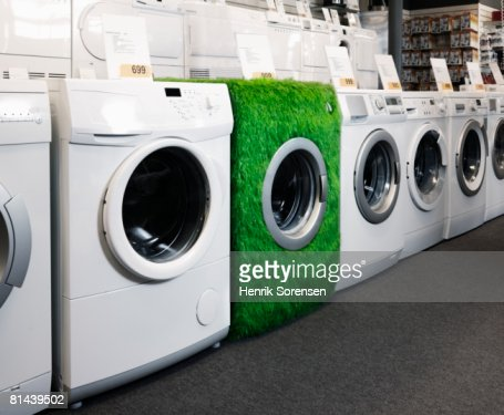 Shop with washers lined up on display and one washer covered with grass.