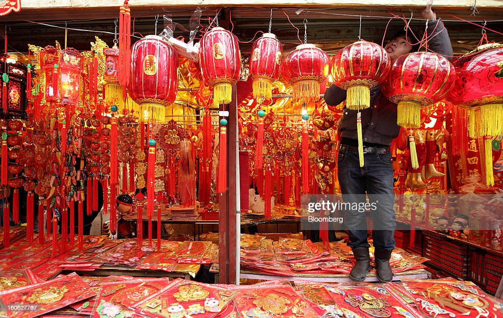 A shop worker arranges lanterns at a store selling Chinese New Year decorations near Yu Garden in Shanghai, China, on Saturday, Feb. 2, 2013. China's services industries grew at the fastest pace since August as gains in retailing and construction aid government efforts to drive a recovery in the world's second-biggest economy. Photographer: Tomohiro Ohsumi/Bloomberg via Getty Images