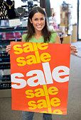 Shop worker holding up sale sign