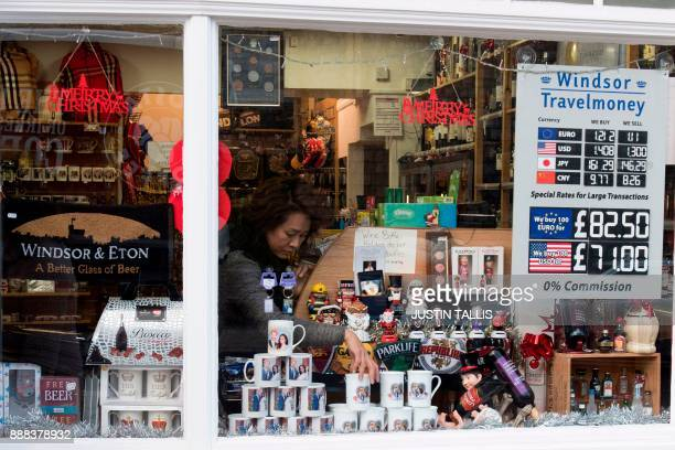 A shop worker makes adjustments to memorabilia celebrating the engagement of Britain's Prince Harry to fiancée US actress Meghan Markle in a gift...