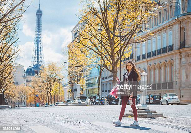 Shopacolic young woman walking with shopping bags in Paris