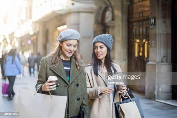 Shopaholic female friends talking on sidewalk