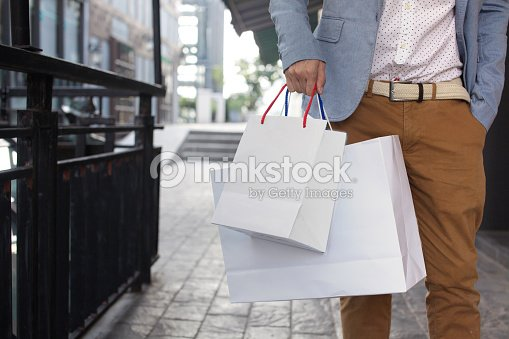 Shopaholic man walking on commercial street with shopping bags
