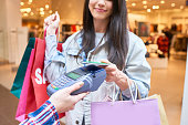 Smiling satisfied young shopaholic holding paper bags and paying for clothing with smartphone in clothing store