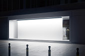 Side view of empty glass shopfront with blank white billboard at night. Retail  concept. Mock up, 3D Rendering