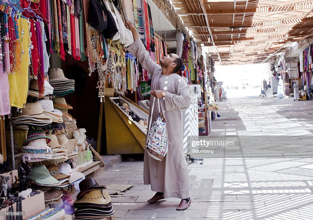 A shopkeeper arranges a display of souvenir tourist items outside his store in Luxor, Egypt, on Thursday, April 25, 2013. Egypt ranked last in terms of security and safety on the World Economic Forum's 2013 Travel and Tourism Competitiveness Index. Photographer: Shawn Baldwin/Bloomberg via Getty Images